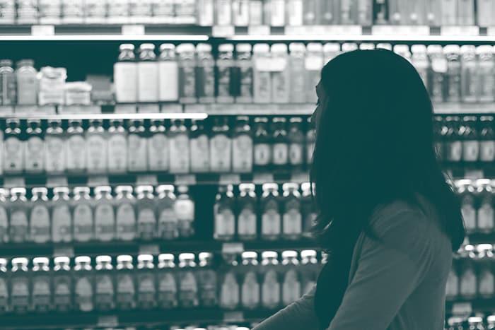 une femme avec un caddie dans un rayon de magasin
